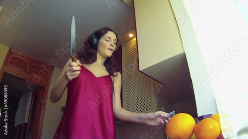 Woman cutting and eating orange while listening to music