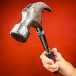 Hand holding a hammer on a bright red background