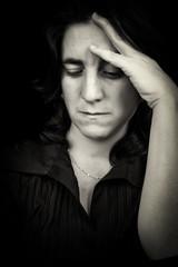 Black and white portrait of a sad hispanic woman with a headache
