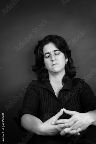 Black and white portrait of a sad woman sitting on the floor