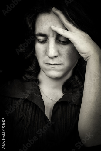 Black and white portrait of a sad hispanic woman with a headache
