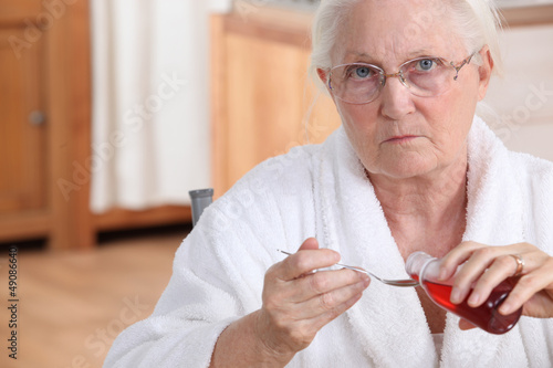 Elderly lady taking medication in kitchen