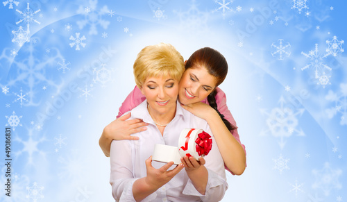 Young woman with her mother on winter background