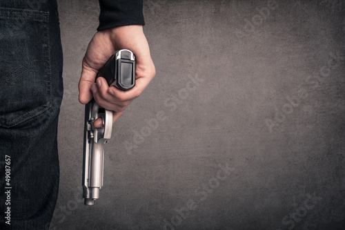 Killer with gun close up over grunge background with copyspace. - 49087657