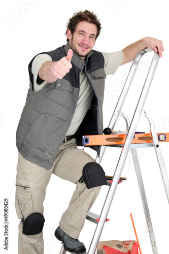 Tiler climbing ladder whilst giving the thumbs-up
