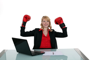 Woman in the office with boxing gloves