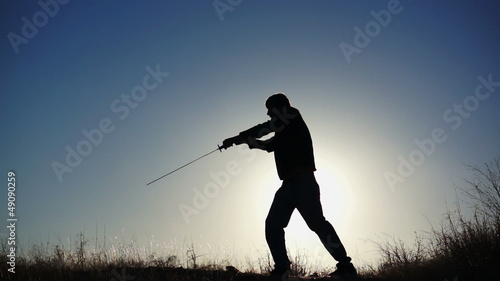 Silhouette of Guy Practicing With Sword