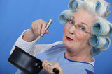 Cheeky older woman in rollers whisking sauce