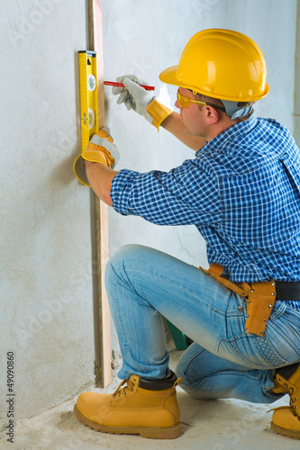 a worker layering on concrete wall