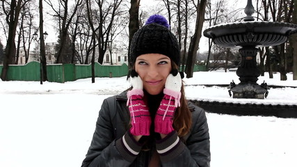 The young girl plays and smile in winter park