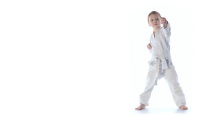 Karate boy exercising isolated against white background