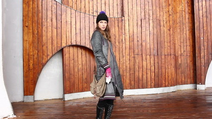 The young girl coquets  the winter on the street