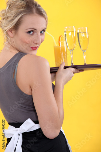 Attractive waitress serving drinks