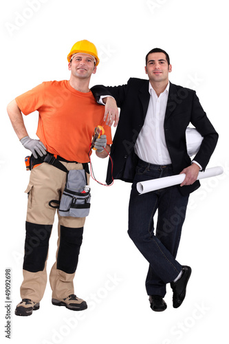 Engineer and construction worker standing side by side