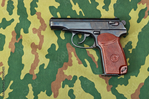 Army handgun on camouflaged background
