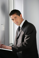 Confident businessman using a laptop
