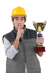 A construction worker shushing while having a trophy cup