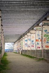Camino de tierra con grafiiti en las columnas