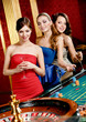 Women keeping glasses of spirits play roulette