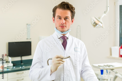 Dentist in his surgery, he holds a drill