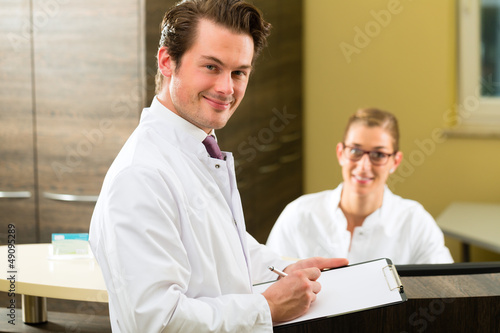 Dentist with clipboard in his surgery
