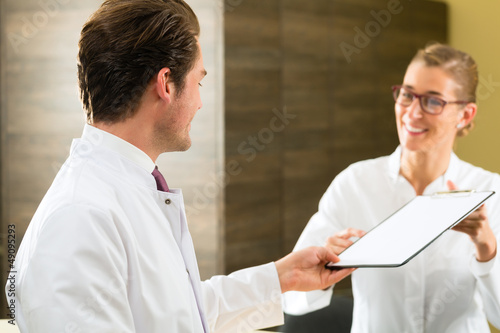 Dentist and nurse with clipboard in clinic