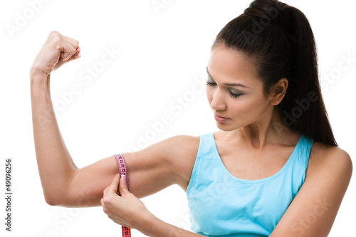 Sportive woman measures her bicep with measuring tape