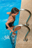 Young girl climbing out of swimming pool