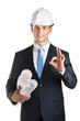 Engineer in hard hat hands blueprints and gestures Okay