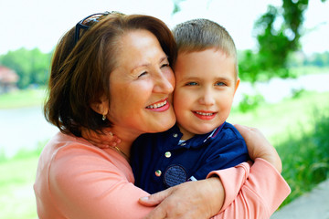 happy grandmother with grandson having fun outside