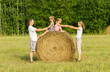 Happy family with child on haystack in sunny day