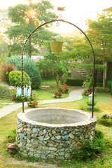 Old Well with a bucket in beautiful garden