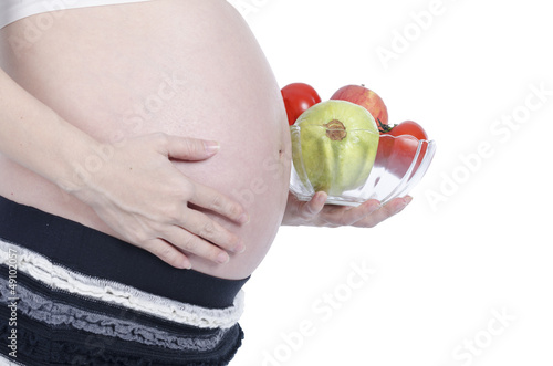 Pregnant woman with fresh fruit isolated over white background