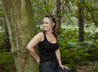 attractive woman in woodland setting leaning against a tree