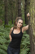 attractive woman standing in woodland leaning against a tree