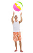 Full length portrait of young man playing with beach ball