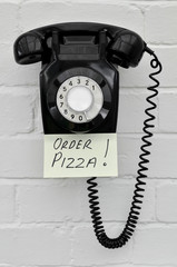 Black retro telephone with reminder note to order pizza