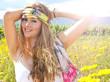 Fröhliche, junge Frau mit buntem Band auf Sommerwiese