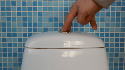 The hand presses the button on the toilet