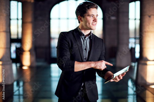 Homme souriant pointant une tablette