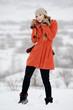 Młoda dziewczyna w pomaranczowym płaszczu na śniegu