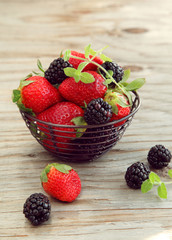Fresh berries in a small metal basket
