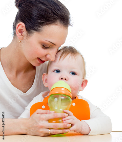 young mother giving drink to baby from feeding cup
