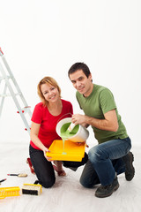 Young couple painting their home