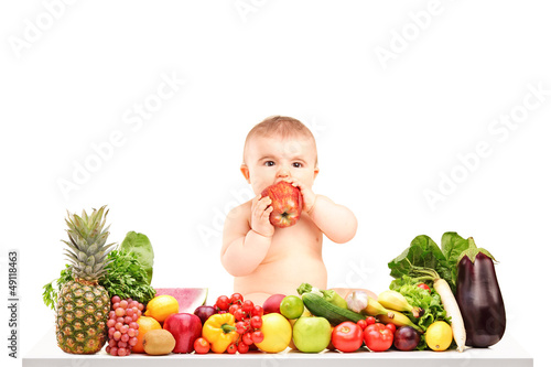 Cute baby boy sitting on a table with fruits and vegetables and