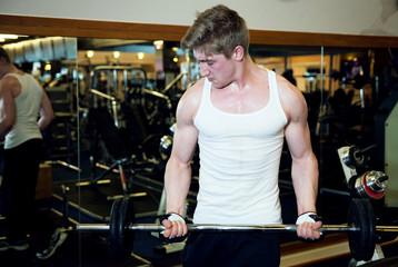 Homme soulevant une barre droite avec des poids
