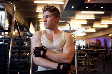 Homme musclé bras croisés dans une salle de musculation