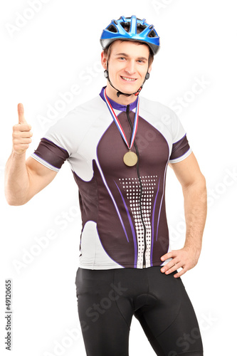 Winner male cyclist with a golden medal giving a thumb up