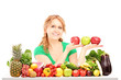 Woman sitting behind a table full of fruit and vegetable and hol