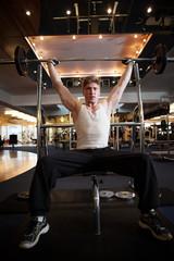 Homme assis soulevant un poids